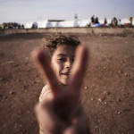 A Syrian girl flashes the victory sign at a refugee camp near the Turkish border in Azaz, Syria, ...