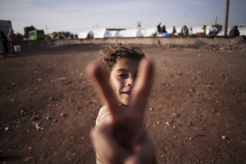 A Syrian girl flashes the victory sign at a refugee camp near the Turkish border in Azaz, Syria, in October 2012. She had fled her home with her family due to fighting between government forces and rebels.