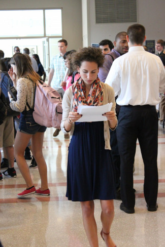 A Student Reads Project Information at the 2014 Pro Bono Sign Up Fair