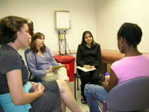 A law student, pediatrician, and social work student meet with a client.
