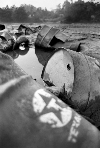 "Oil barrels left on the banks of the Aguarico River, near Lago Agrio, from the film ""Crude."" (Credit: Kayana Szymczak.)"